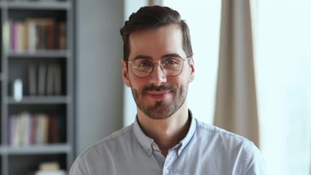 leende stilig ung affärsman bär glasögon tittar på kameran - porträtt man bildbanksvideor och videomaterial från bakom kulisserna