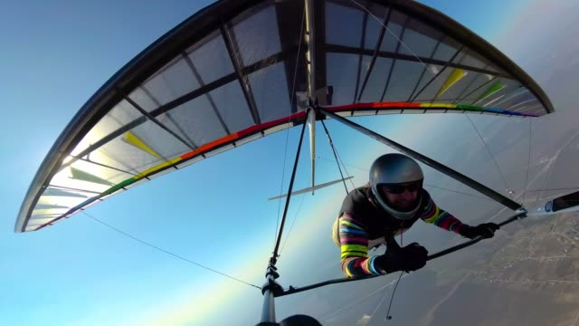 Smiling hang glider pilot shows thumb up while flyingh high above ground