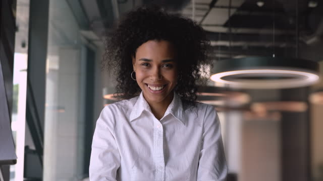 smiling happy african american mixed race businesswoman talking consulting client online - głowa filmów i materiałów b-roll