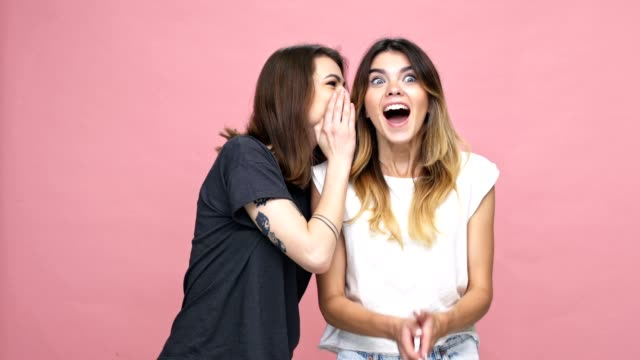 smiling happy girl whispering a secret to her female friend and they giving high five isolated over pink background - приватность стоковые видео и кадры b-roll