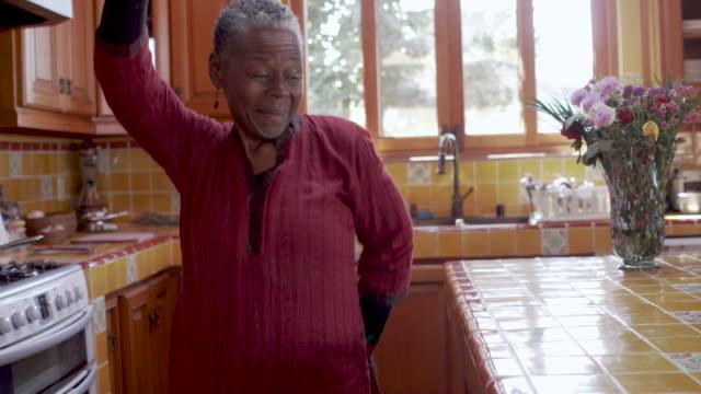 sorridente felice donna nera matura che balla e celebra la vita nella sua cucina - donne mature video stock e b–roll