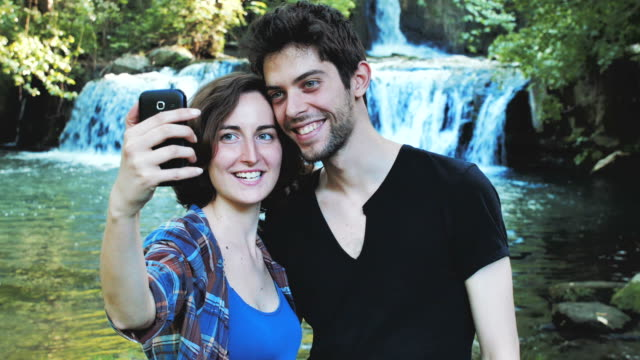 vídeos de stock e filmes b-roll de smiling happy people in the nature with waterfall in background - man admires forest