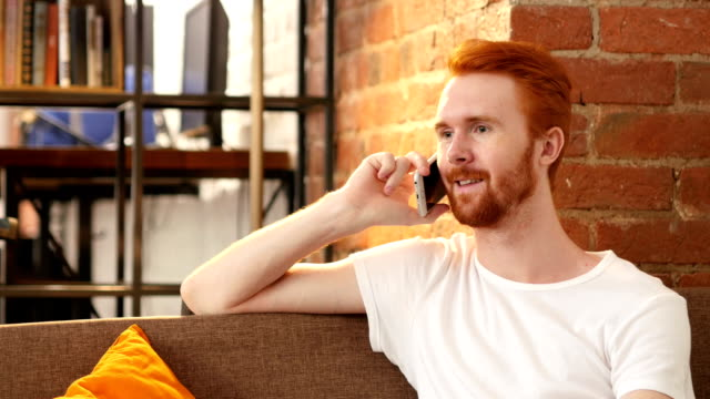 smiling happy red hair man getting good news on the phone video
