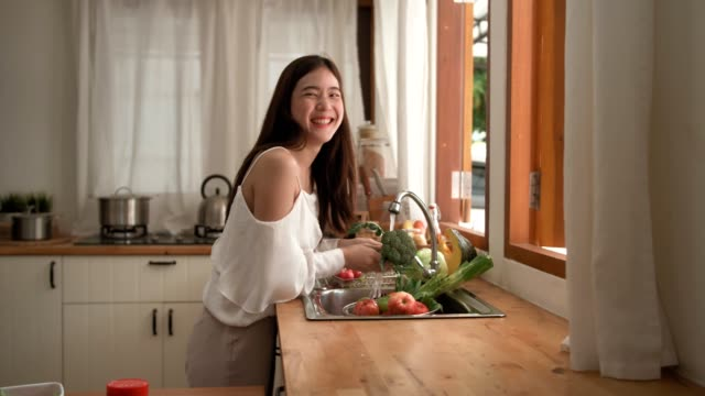 Smiling happy woman washing vegetbles at home during COVID-19 coronavirus outbreak