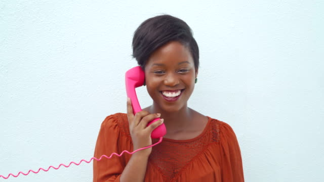 Smiling happy young woman talking on the pink telephone video