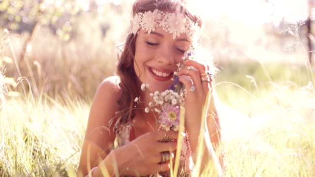 Smiling hippie girl in a park holding wild flowers video