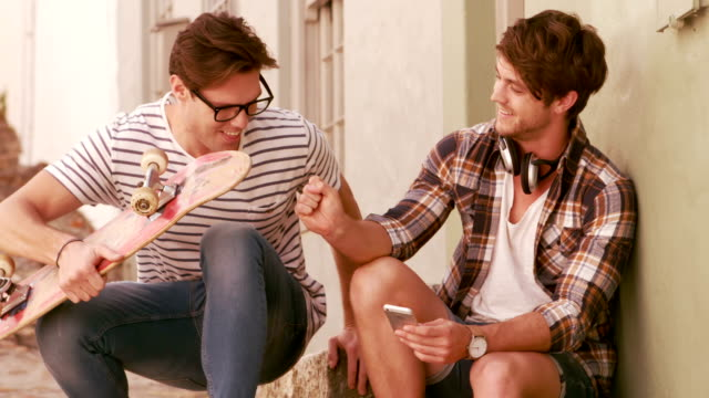 Smiling hipster friends sitting together while holding skateboard video