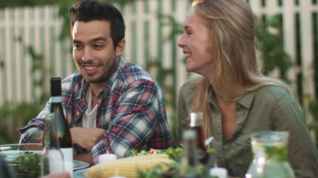 vídeos y material grabado en eventos de stock de sonriente hombre de etnia hispana comunicarse con una joven en la cena familiar al aire libre - árboles genealógicos