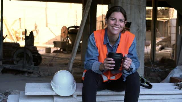 Smiling Hispanic female engineer holding coffee mug at site