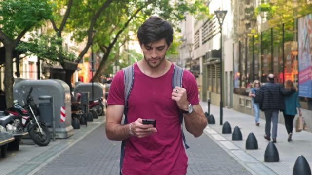turista maschio ispanico sorridente che cammina con lo smartphone - argentina america del sud video stock e b–roll