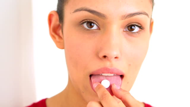Smiling Hispanic woman taking a pill video