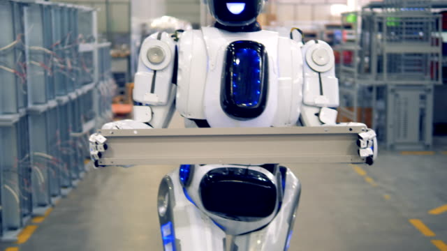 smiling humanoid is carrying a piece of metal fitting in a factory. - rivoluzione industriale video stock e b–roll