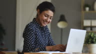 istock Smiling indian girl student typing on laptop preparing course work 1180677557