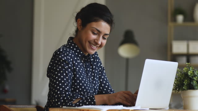 Video Smiling indian girl student typing on laptop preparing course work