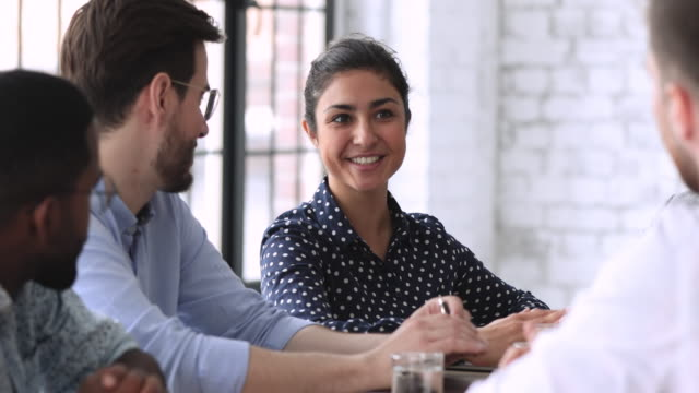 Smiling indian hr member talking to job applicant during interview
