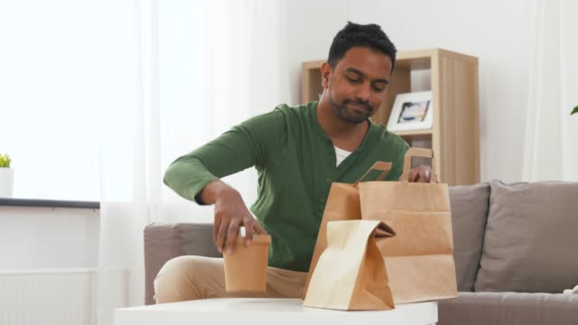 lachende Indiase man uitpakken afhaalmaaltijden thuis video