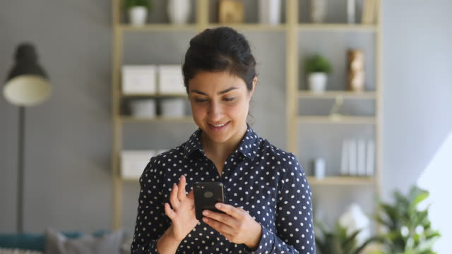 Smiling indian young woman using mobile apps holding smart phone Smiling indian ethnic young woman using mobile apps holding smart phone looking at cellphone screen playing games texting messages enjoy social media applications in smartphone at home office mobile app stock videos & royalty-free footage