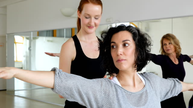 Smiling instructor assisting women at yoga class video