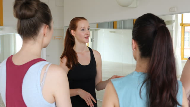 Smiling instructor talking to women at yoga class video