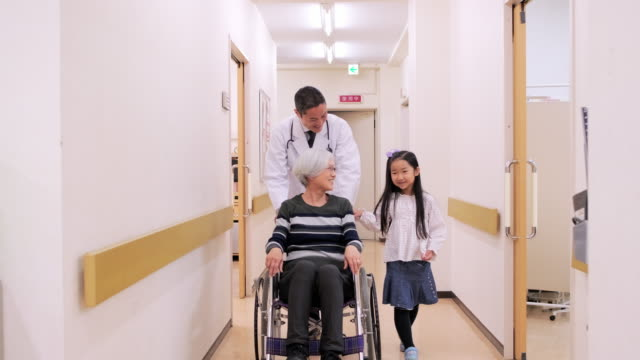 Smiling Japanese Doctor and Grandmother with Granddaughter Video shot of mid adult male Japanese doctor pushing smiling grandmother in wheelchair and young granddaughter walking alongside. pushing wheelchair stock videos & royalty-free footage