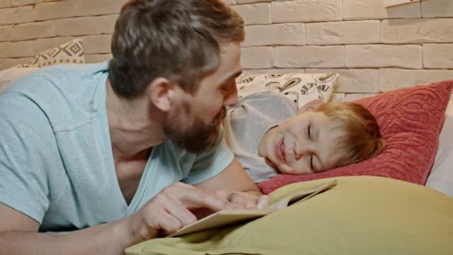vídeos y material grabado en eventos de stock de sonriente niño escuchando papá libro de lectura en la cama - madre e hijos