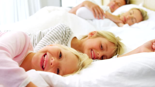 Smiling kids relaxing on bed while parents sleeping in background 4k video