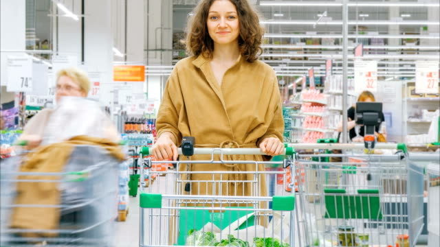 smiling lady in brown coat stands in department store - vídeo