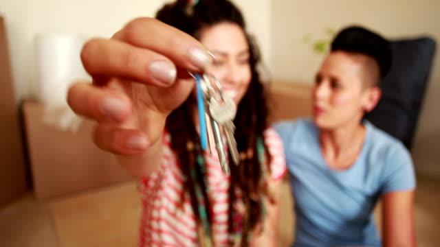 Sorridente casal Lésbico mostrando novas chaves - vídeo
