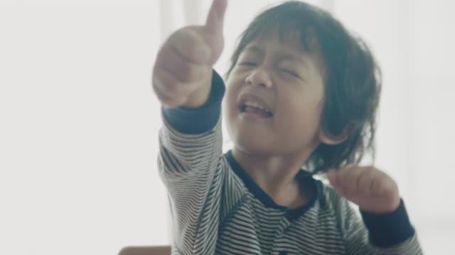 lächelnder kleiner junge essen in der nähe - 2 3 jahre stock-videos und b-roll-filmmaterial