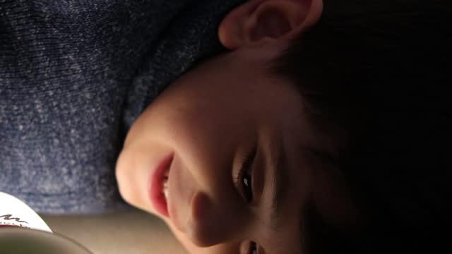 leende liten pojke gömmer sig under filt - duntäcke bildbanksvideor och videomaterial från bakom kulisserna