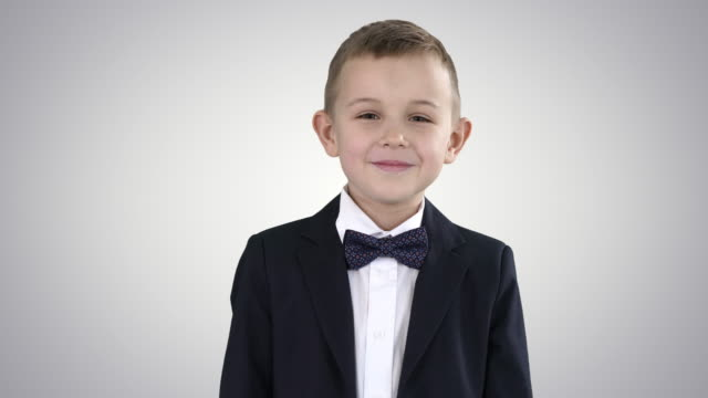 smiling little boy in formal clothes standing on gradient background - scolaro video stock e b–roll