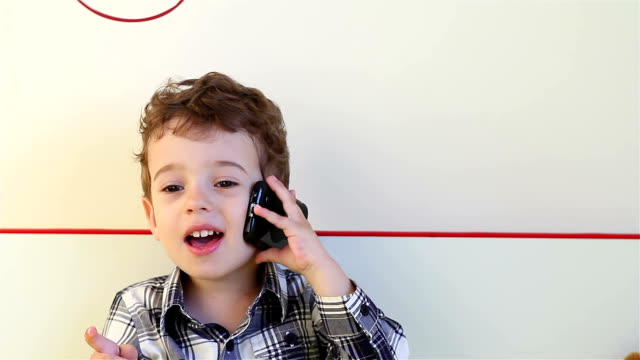 Smiling little boy talking on smartphone Laughing little boy talking on smartphone at home one boy only stock videos & royalty-free footage
