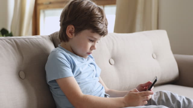 smiling little child playing online games on smartphone. - solo un bambino maschio video stock e b–roll