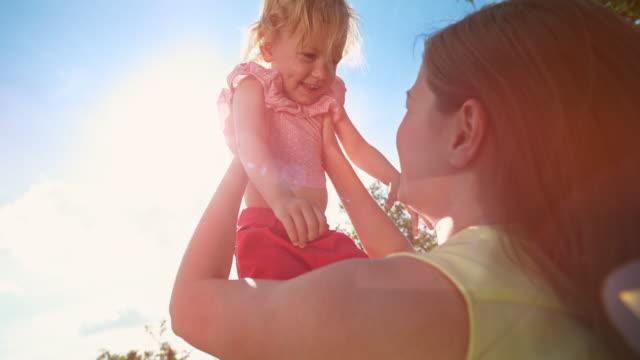 slo mo leende liten flicka som tagits upp av hennes mamma in i himlen i solsken - enbarnsfamilj bildbanksvideor och videomaterial från bakom kulisserna