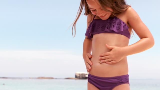 smiling little girl touching her belly - купальный костюм стоковые видео и кадры b-roll