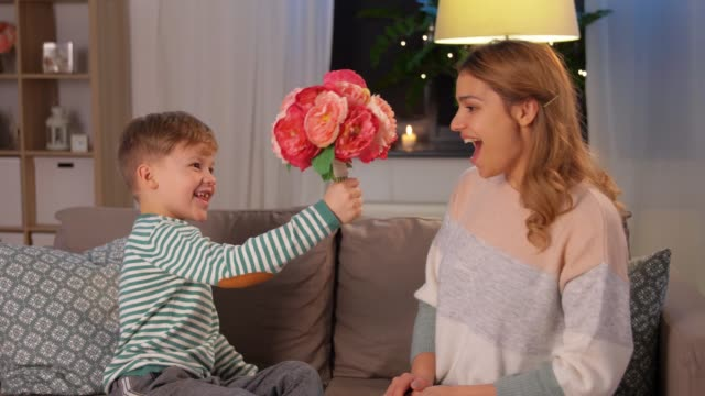 smiling little son gives flowers to mother at home mother's day, holidays and family concept - happy little son giving flowers, kissing and hugging his mother at home in evening bunch stock videos & royalty-free footage