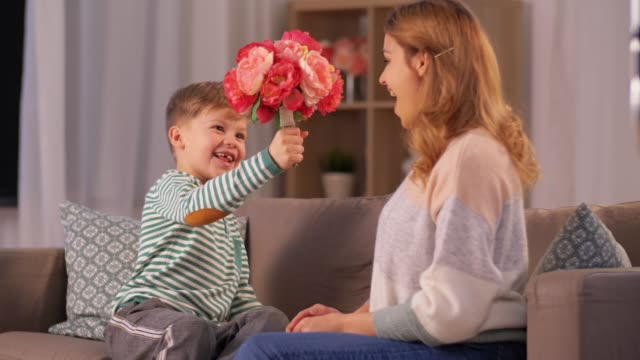 smiling little son gives flowers to mother at home