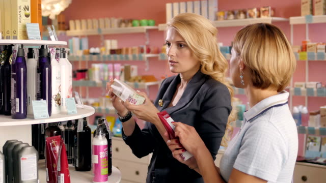 Smiling longhaired girl friend choosing shampoo at supermarket. Females shopping Cosmetics shop video