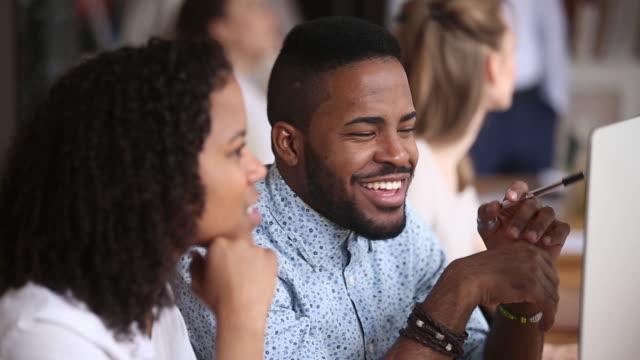 vidéos et rushes de employé africain de sourire écoutant le collègue féminin s'asseyant dans le bureau - workshop