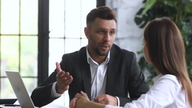 vidéos et rushes de le banquier mâle de sourire consultent le client féminin font l'accord de signe d'accord - relation client
