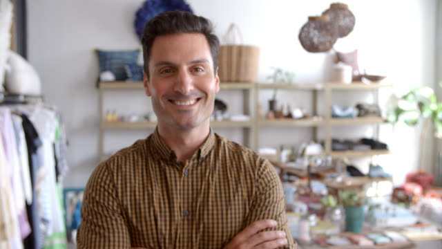 Smiling male business owner in boutique walks into focus video