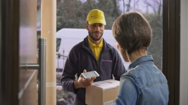 Smiling male courier delivering a package to the female customer's house