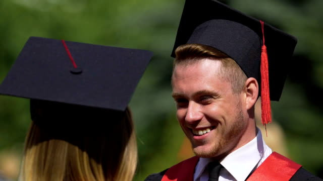 Smiling male graduate talking to friend at graduation party, happiness and joy video
