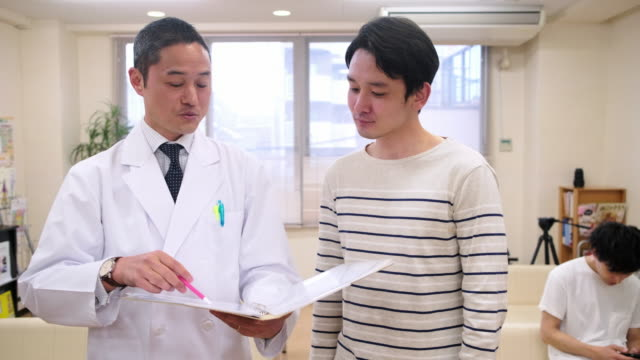 笑顔男性日本医師安心男性患者 - 東アジア点の映像素材/bロール