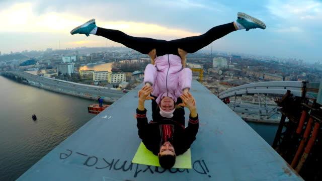 smiling man and woman doing acrobatic yoga stunts on bridge, adrenaline junkies - время дня стоковые видео и кадры b-roll
