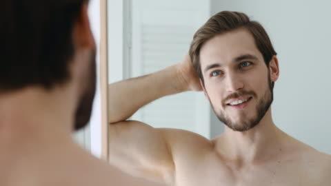vidéos et rushes de homme de sourire peignant des cheveux avec des doigts, se préparant dans la salle de bains. - personnes belles
