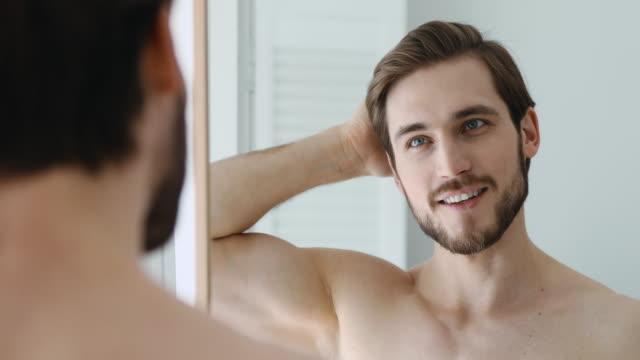 lächelnder mann kämmt haare mit denfingern, immer bereit im badezimmer. - gutaussehend stock-videos und b-roll-filmmaterial