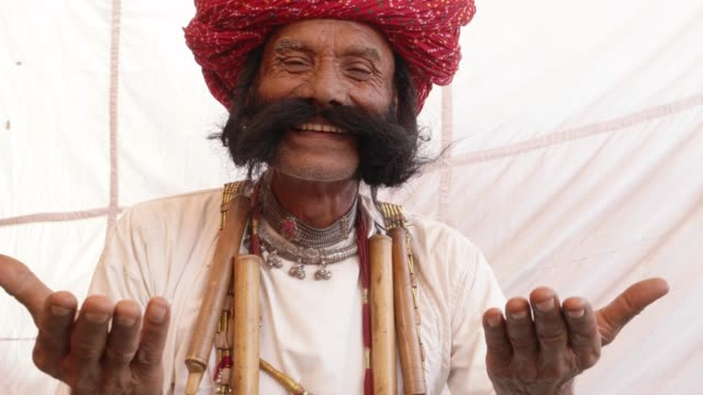 vídeos de stock e filmes b-roll de smiling man from rajasthan with big moustache and hands joined in namaste welcoming guests - hinduísmo
