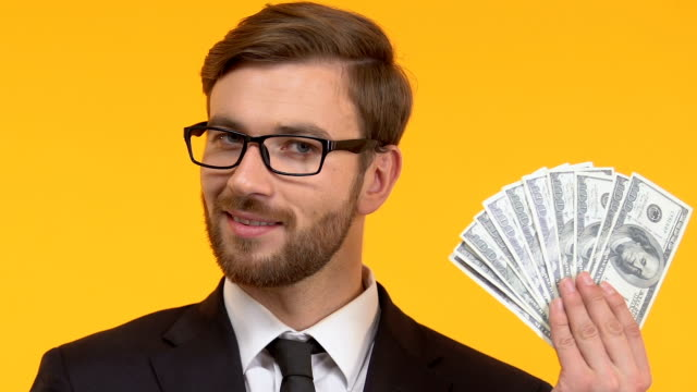 smiling man holding cash in hand, perks and bonuses, isolated bright background - bonus video stock e b–roll