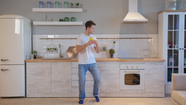 smiling man in white t-shirt dancing on the kitchen - maglietta video stock e b–roll